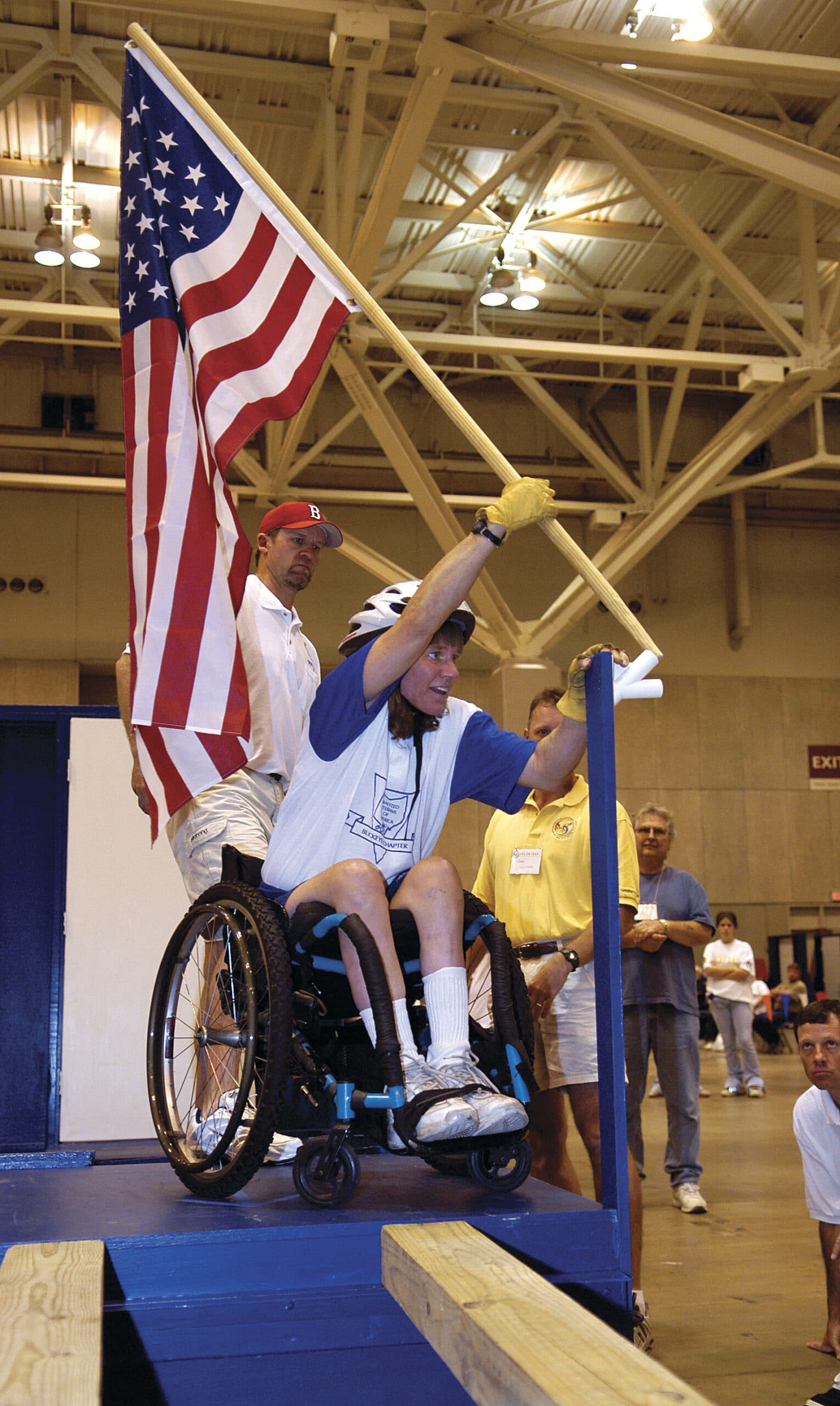 """Holly Koester, OH, a guest competitor in the """"Super G"""" places the American Flag in the holder near the finish line. 4th National Veterans Wheelchair Games, St. Louis. Missouri - June 15-19, 2004. PVA/ Sports"""