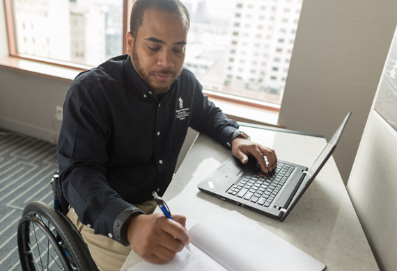 A veteran in a wheelchair works at a computer.